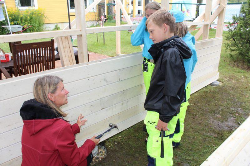 Ordføreren rådfører seg med de erfarne hagestue-byggerne fra Byggeskolen.